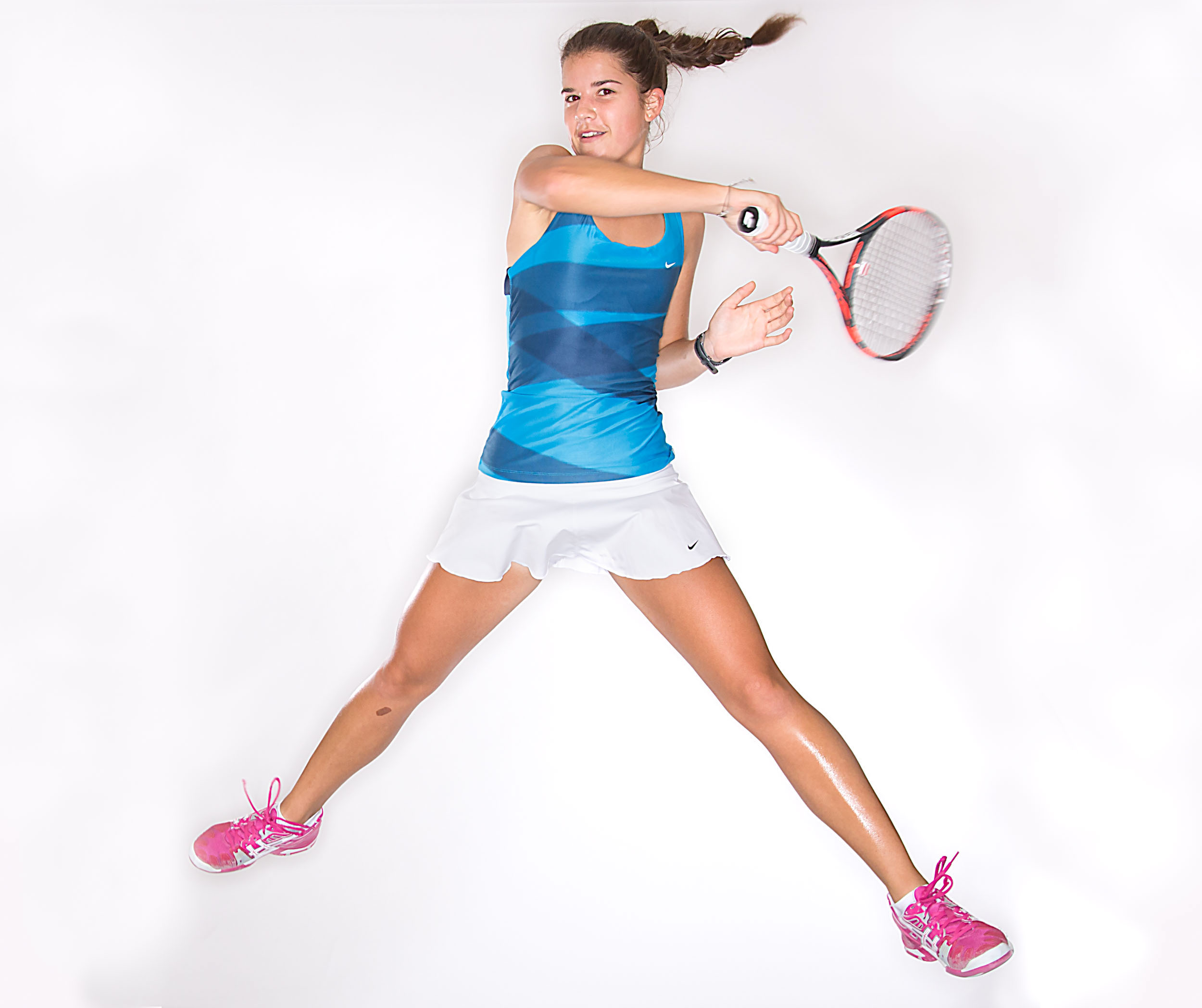 Studio action photo of girl playing tennis, magazine sports portrait