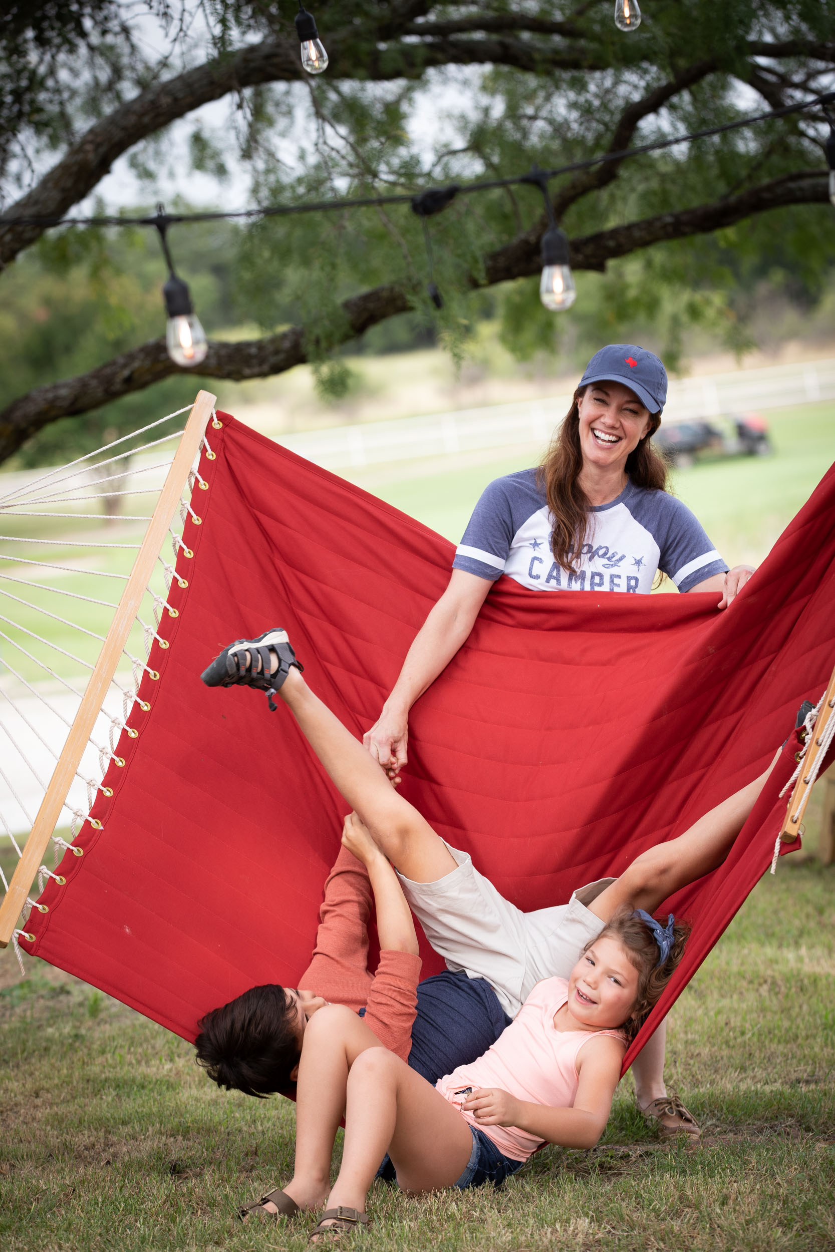 Mom and kids playing in hammock by Steven Martine